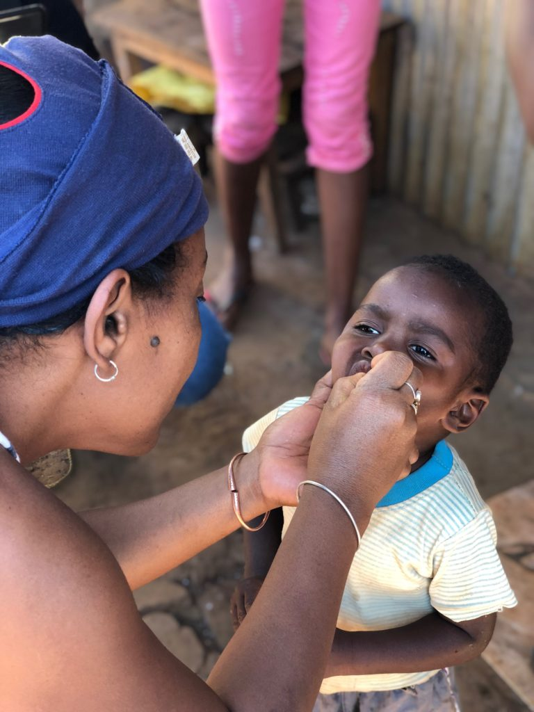 A lady administers vaccine into a little boy's mouth