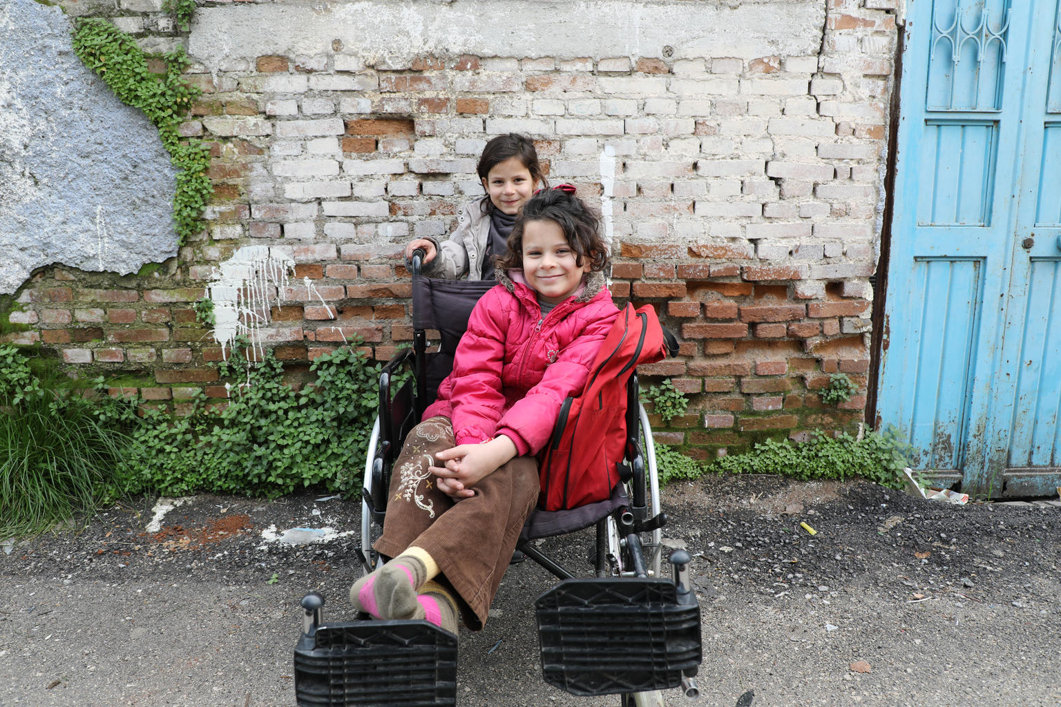 Two young girls - one sitting on, and the other behind a wheelchair.