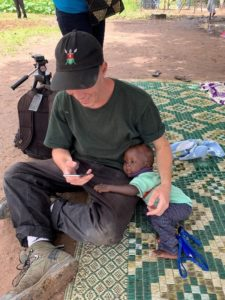 A man sitting cross-legged on the floor looks at his phone while holding on to a small child beside him.