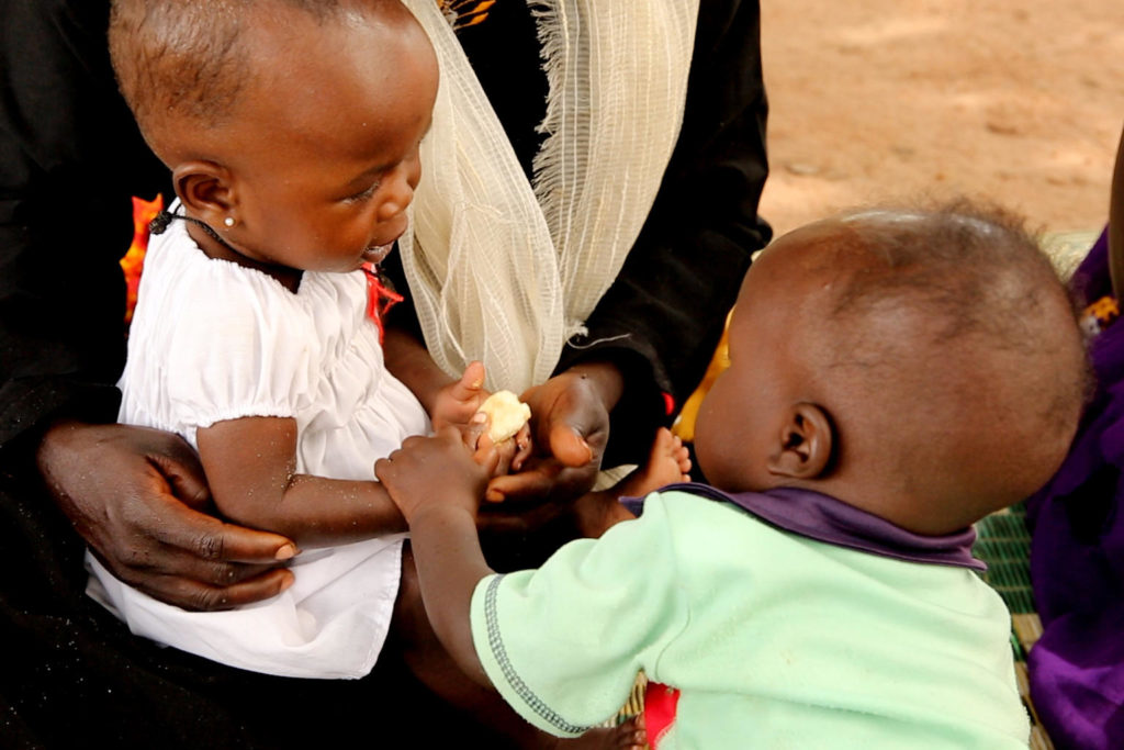 Two infants holding a piece of food.