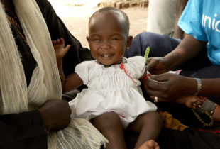 An infant in the arms of her mother smiles as she gets her arm measured by a woman in a UNICEF t-shirt