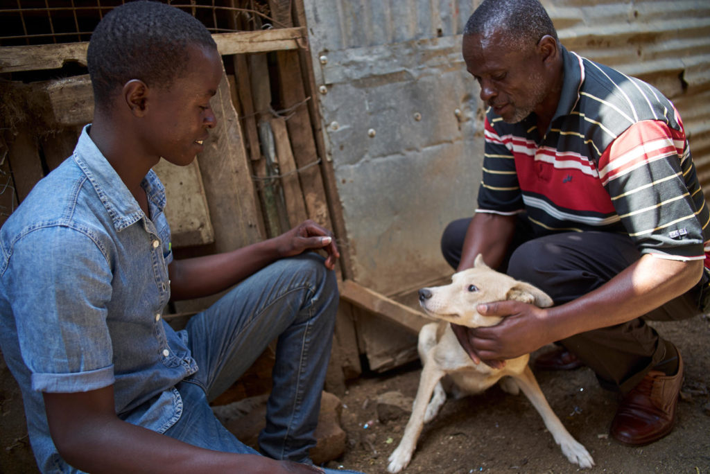 Two men squatting and petting a dog