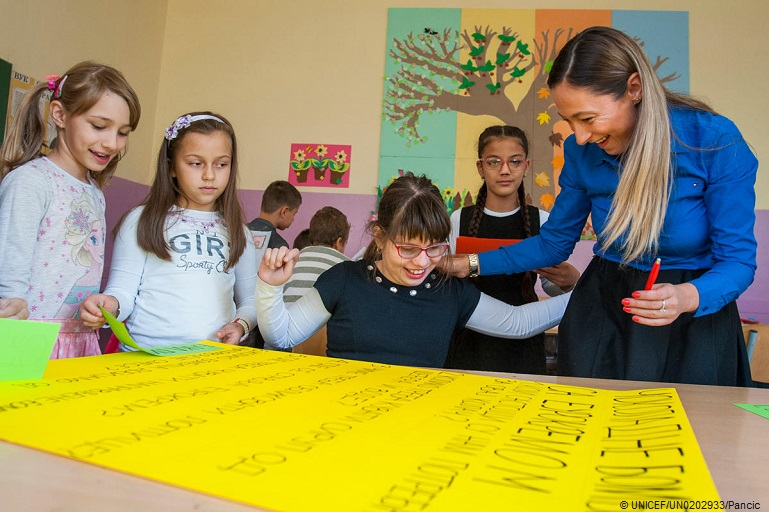 A female teacher with a group of young girls in a classroom