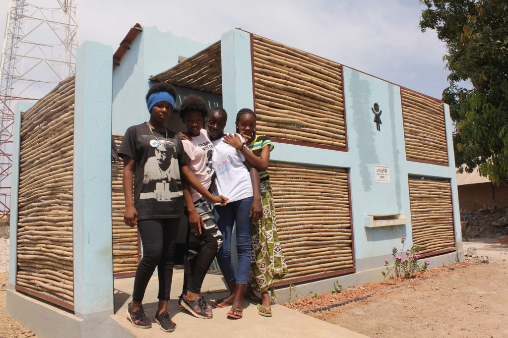 A group of girls standing at the entrance of a newly constructed outhouse.
