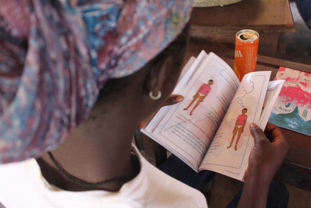 A girl reading a leaflet with illustrations in it.