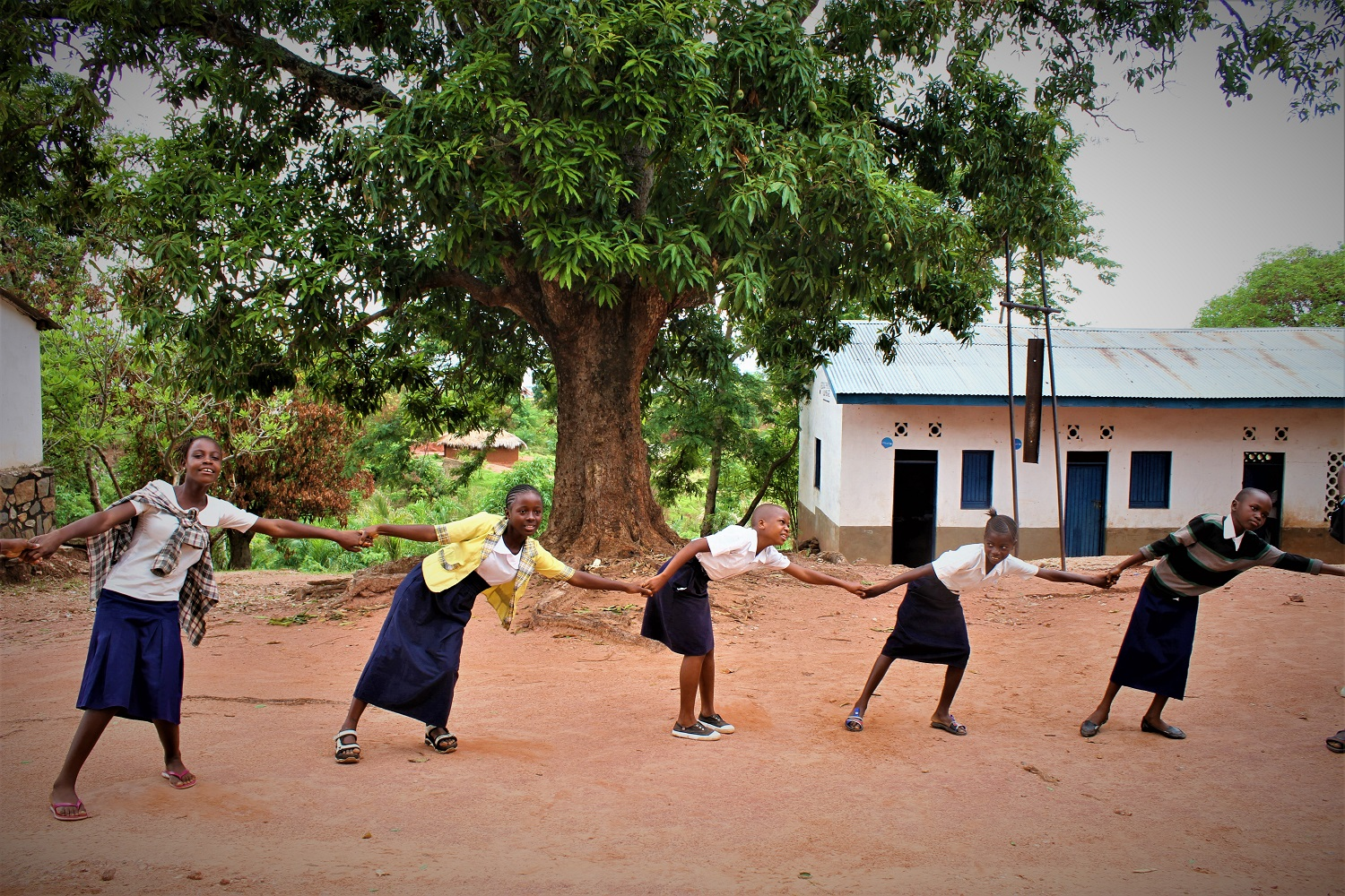 A group of children in school uniform form a human chain in a school yard.