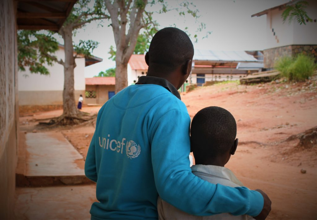 A man in a UNICEF tee shirt with his arms around the shoulder of a young boy. Both look into the distance.