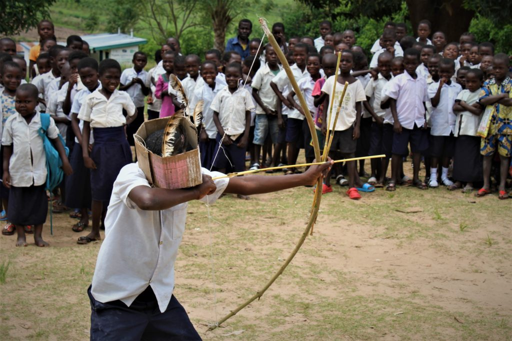 A boy wearing a cardboard box mask takes aim with a bow and arrow as other school children look on.