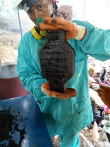 A factory worker in a mask holding up a brick made from recycled plastic.