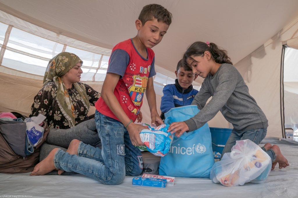 Children opening blue packets on the floor of a tent.