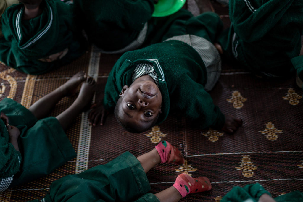 A child looks up toward the ceiling as he sits on a carpeted floor