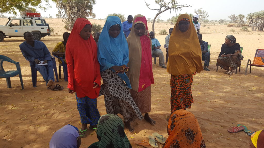 A group of three girls demonstrate to adolescent girls sitting.