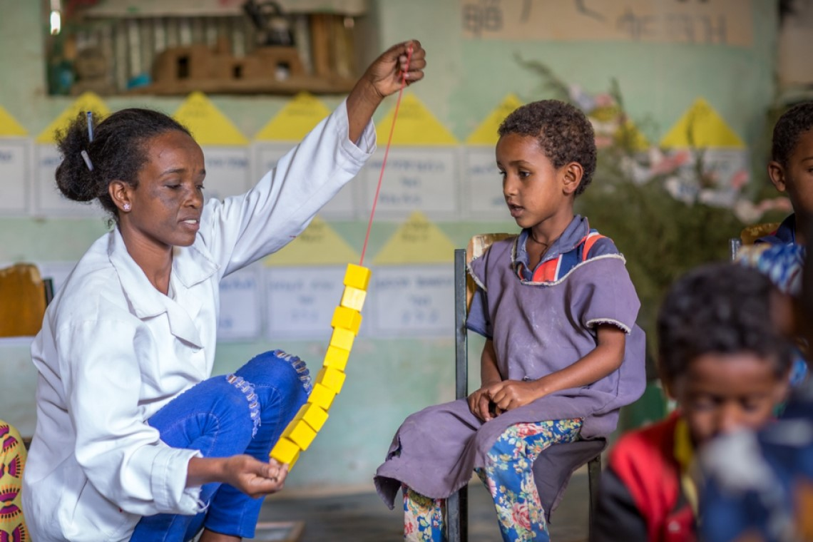 A teacher shows a chain of blocks to her student