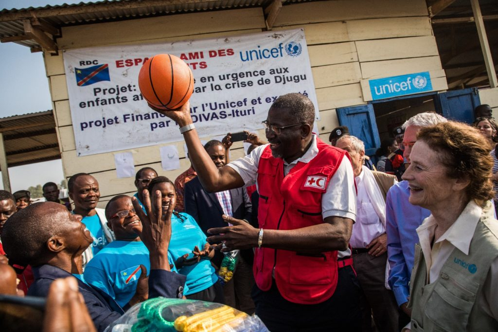 A man holds up a basketball for a group of children with ED Fore beside him.