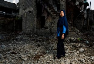 A young woman stand ion front of the rubble of a building