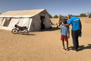 A boy and a young man in front of a unicef tent