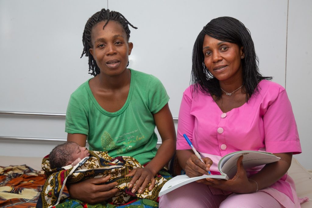 Two ladies holding a baby and pouring over documents.