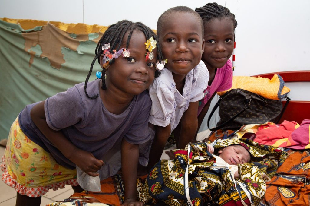 Three smiling children leaning over a swaddled baby.