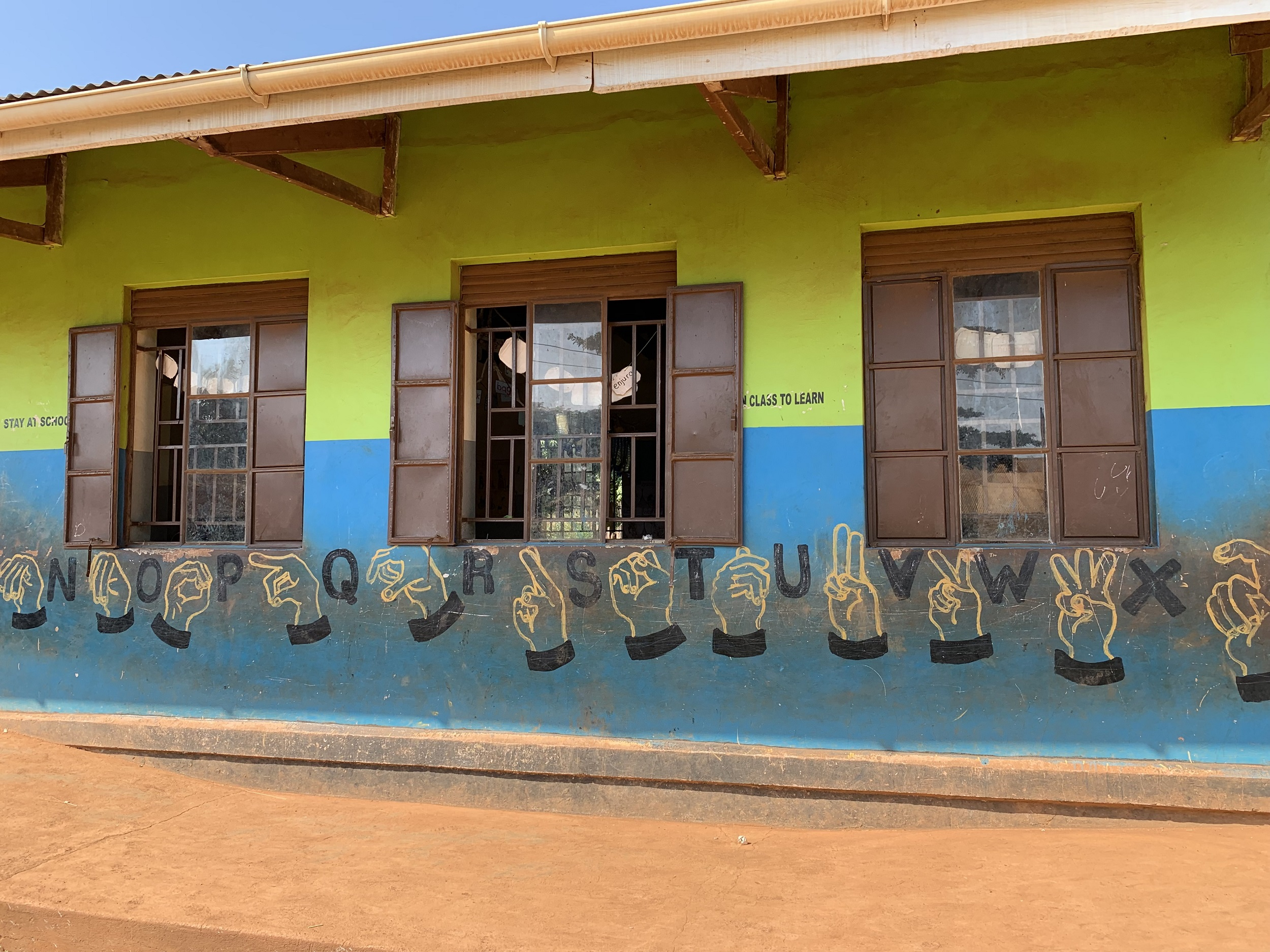 A school wall with windows featuring hand painted sign language and alphabets