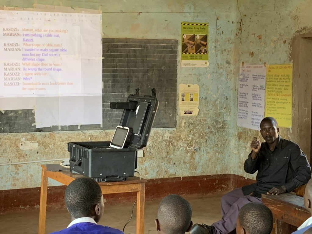 A classroom with a projector in the middle and children and an instructor sitting around it.