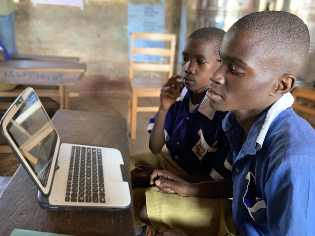 Two boys peering into a small laptop in a classroom.