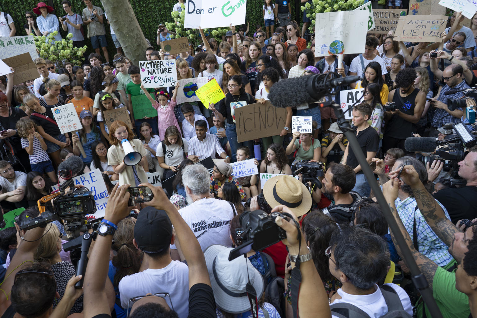 Children protesting in a crowd with cameras facing them