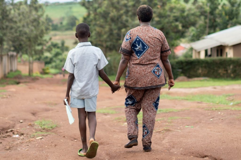 A lady and young boy hold hands as they walk away.