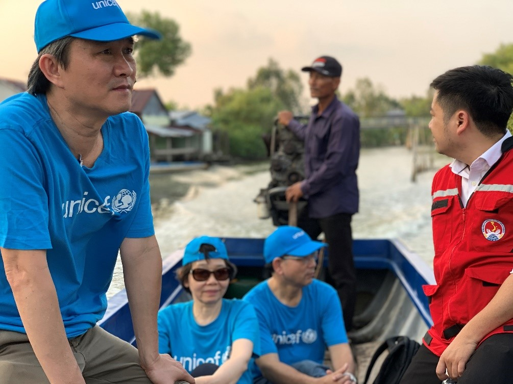 Man in a hat and blue clothse stares out at the river from a boat he shares with others in UNICEF gear,