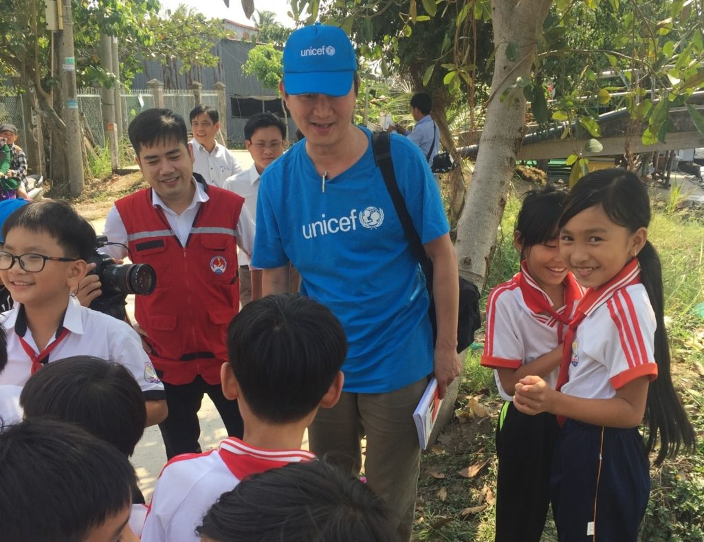 A man in a UNICEF hat and tee shirt interacts with children.