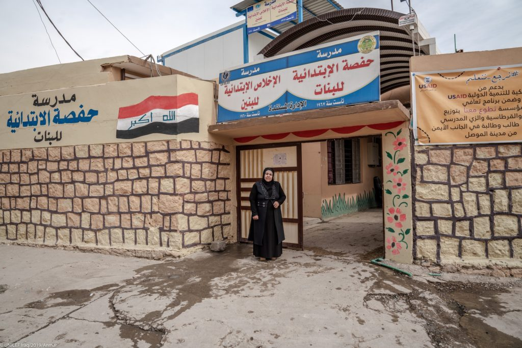 A lady in a hijab stands at the gate of a building with a painted sign atop.
