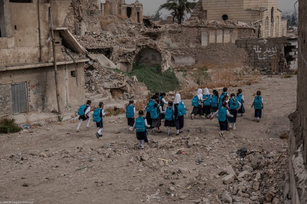 A group of young girls in school uniform walking amidst rubble