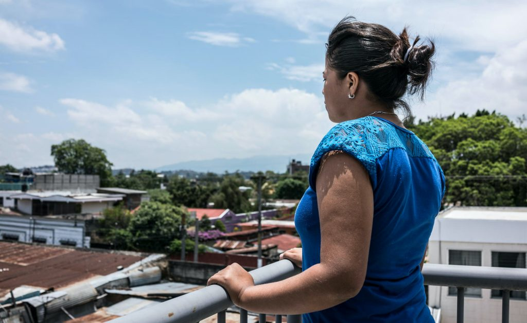 A young woman stands a long on a roof, looking over the city.