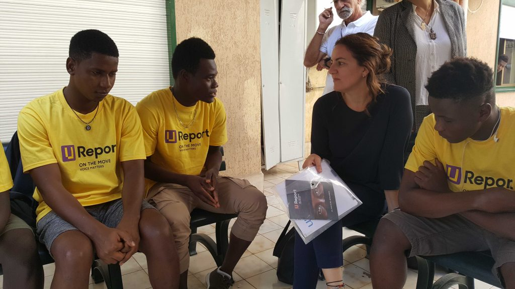 Young men in yellow T-shirts speak with a UNICEF representative.