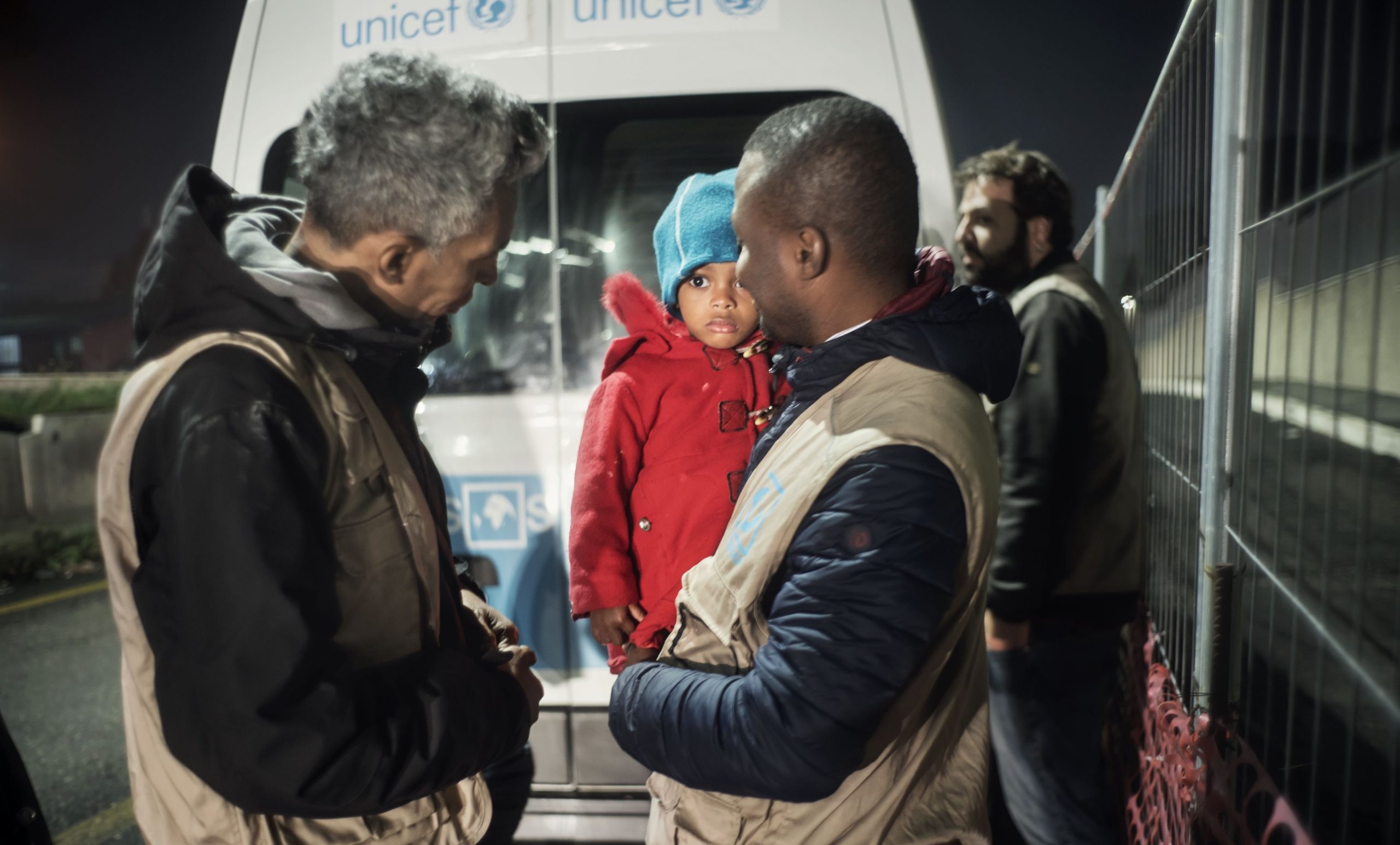 A man hollds a small child in front of a UNICEF van