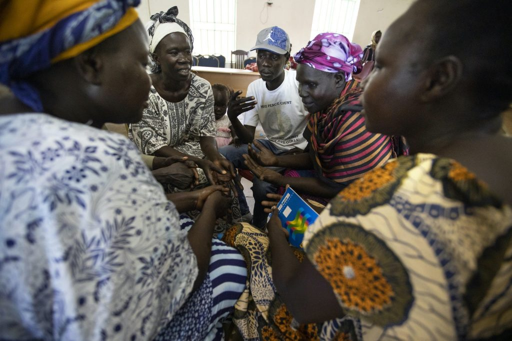 A group of women lean in, talking to each other