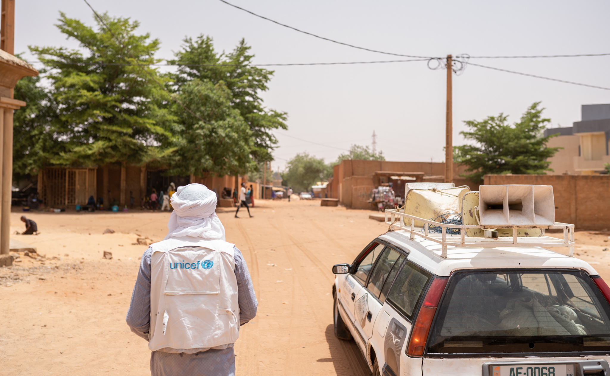 A UNICEF-clad worker on a dusty road.