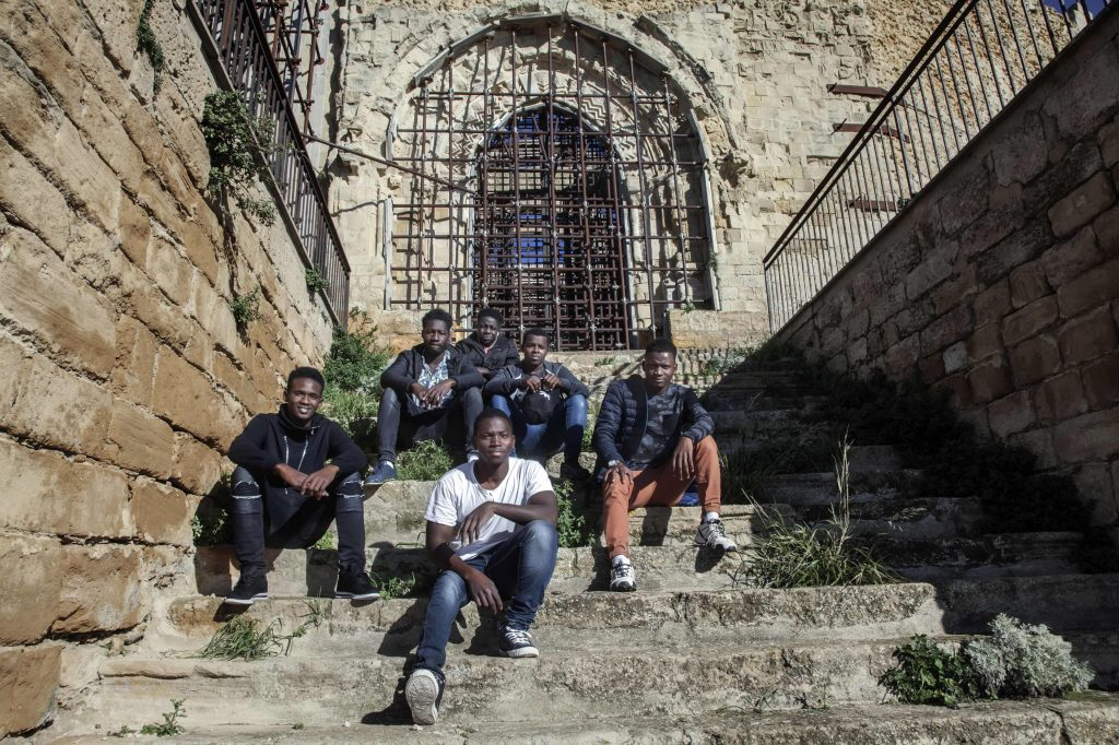 A group of young men sit on ancient stone stairs
