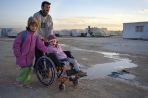 A young girl, being pushed in a wheelchair, by a man and another girl, across muddy ground.
