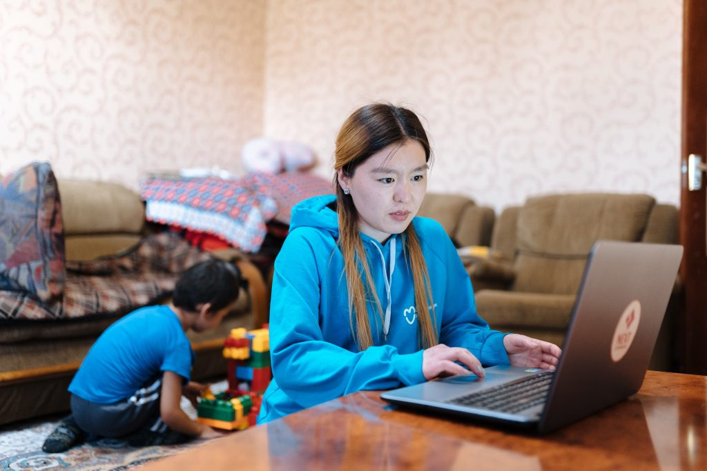 A young woman at a laptop while a boy plays with toys on the floor