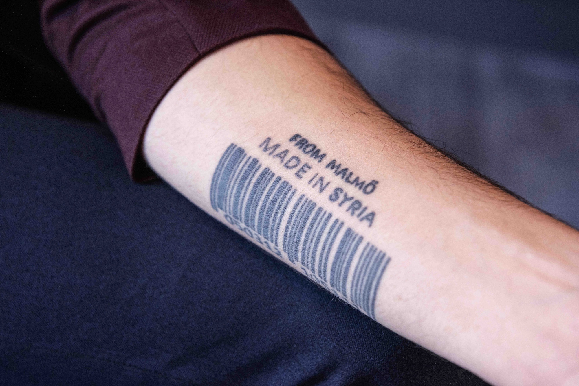 "A man's arm showing a tattoo that says ""Made in Syria."""