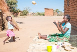 A woman sits on the ground and a child throws her a ball.