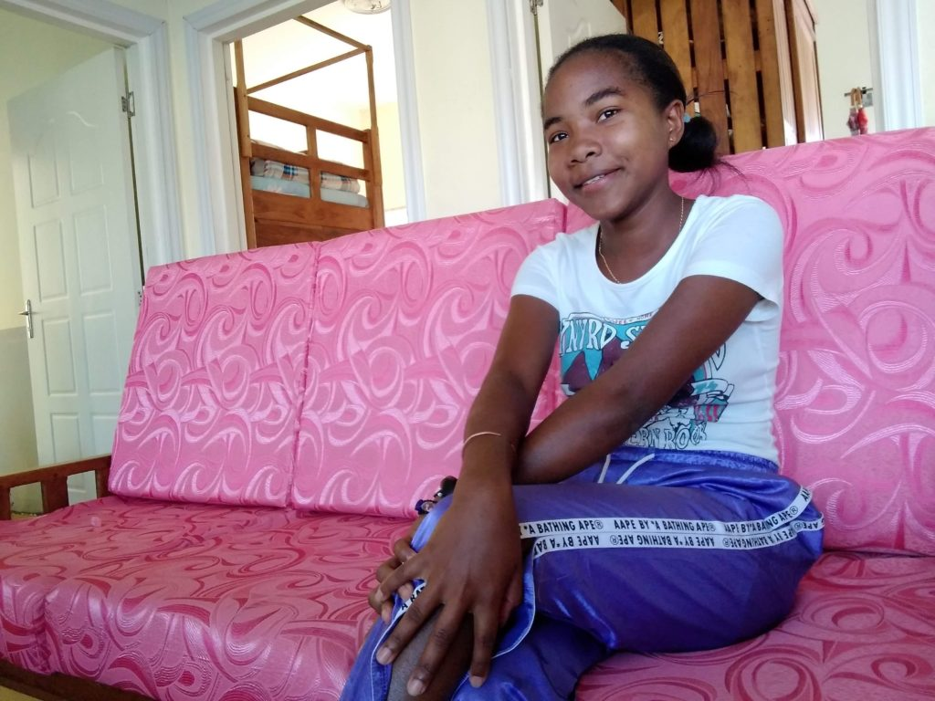 A young girl sitting on her couch