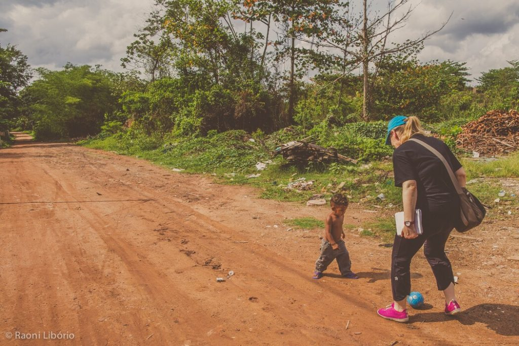A woman stands in a road with a child.