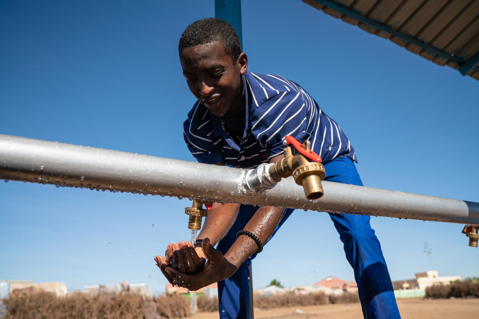 A boy hunched over a water tap, Somaliland.