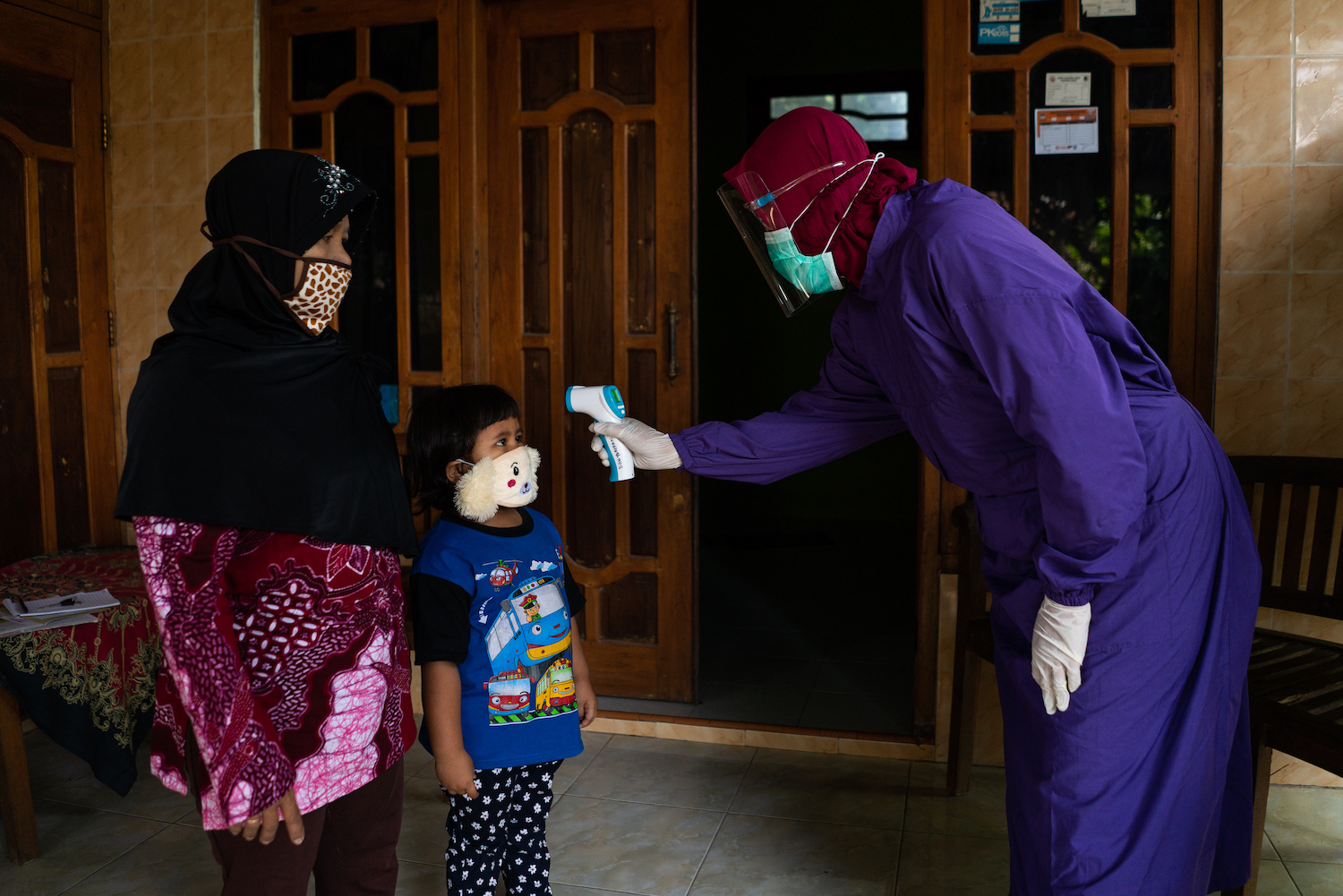 A health worker carries out a temperature check on a child