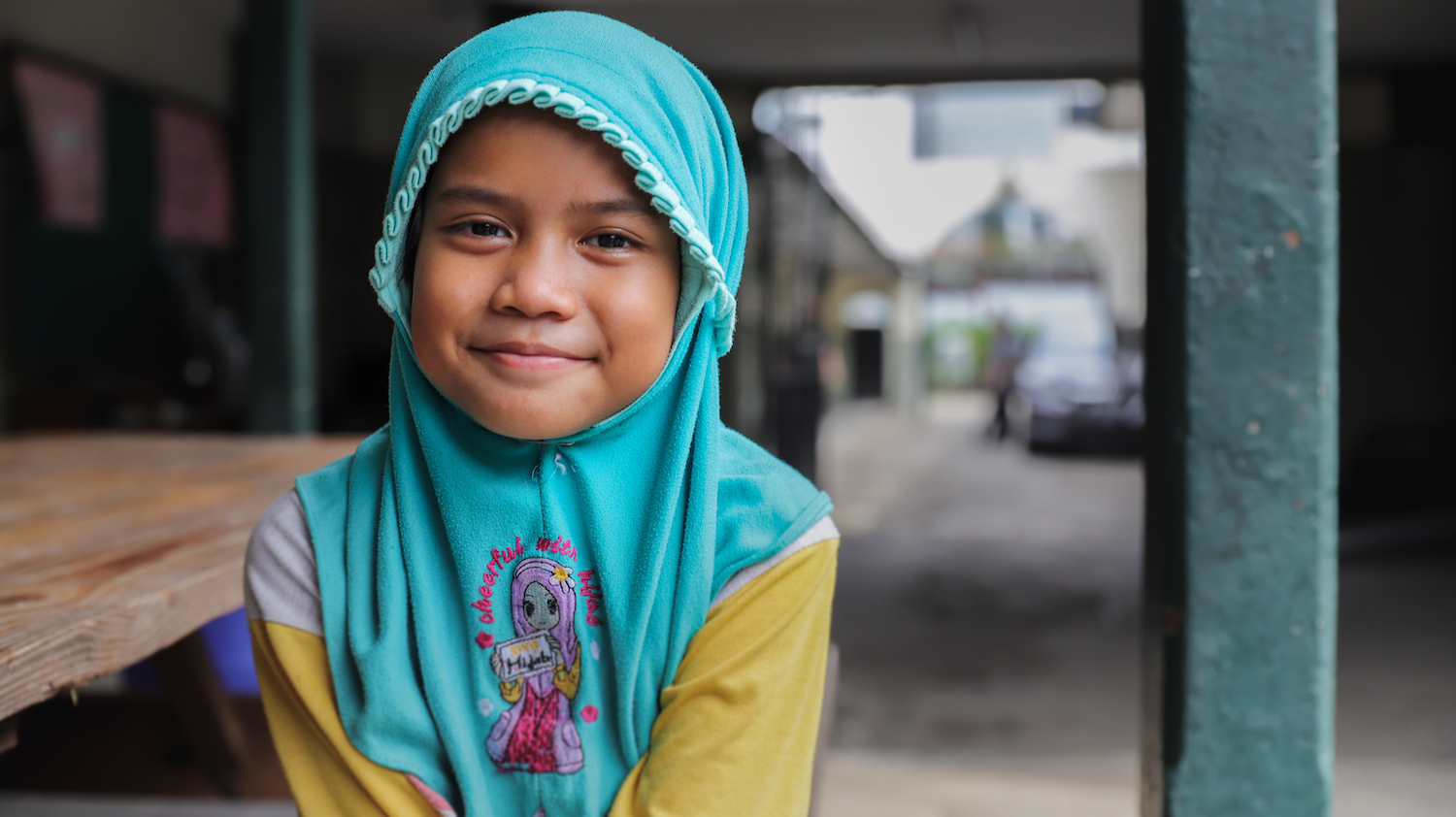 A girl in traditional headgear in an orphanage