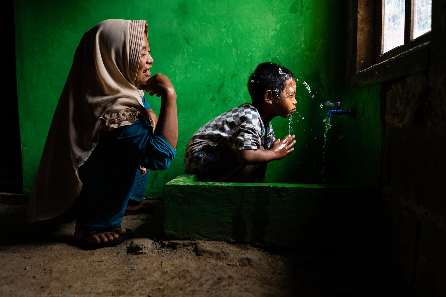 A mother looks on as a child washed his face at a water source in Indonesia.