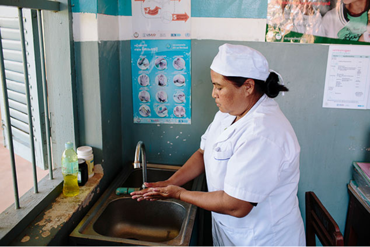 A health worker washes her hands over a sink in a health care facility in Ethiopia