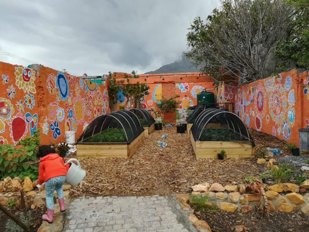 A young girl waters plants inside a community garden