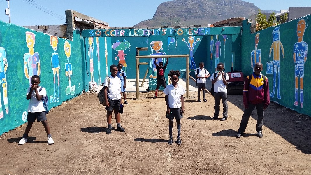 A group of young boys standing in a newly prepared football court